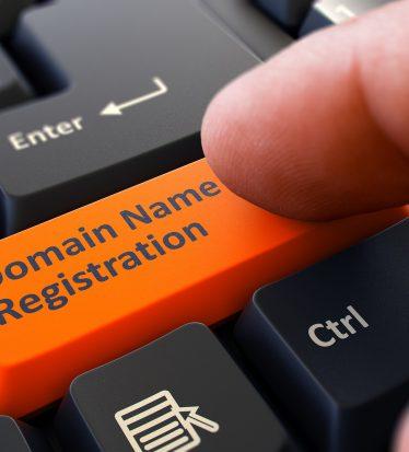 Finger Presses Orange Button  Domain Name Registration on Black Keyboard Background. Closeup View. Selective Focus.